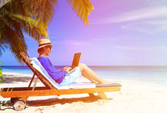 Man with laptop on tropical beach Royalty Free Stock Photos