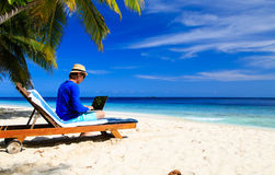 Man with laptop on tropical beach Stock Photos