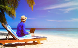 Man with laptop on tropical beach Royalty Free Stock Image