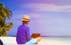 Man with laptop on tropical beach Stock Images