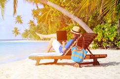 Man with laptop on tropical beach vacation Royalty Free Stock Image