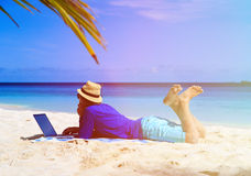 Man with laptop on tropical sand beach Royalty Free Stock Photo