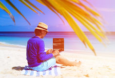Man with laptop on tropical sand beach Royalty Free Stock Photography
