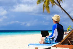 Man with laptop on tropical vacation Stock Photo