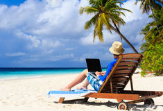 Man with laptop on tropical vacation Stock Photos