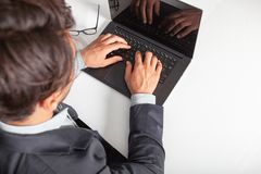 Man with laptop typing on the keyboard. On white table.. stock photo