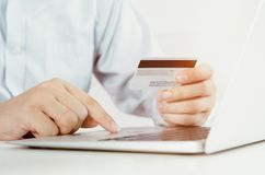 Man with laptop using credit card. Internet shopping. Stock Image