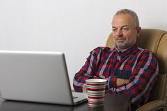 Man at the laptop. Man working at the laptop in the office Stock Image