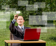 Man with laptop working outdoors Stock Images