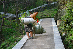 Man with large bales on the steps in the Wudang Mountains Stock Photography