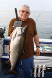 Man with Large Fish - King Salmon. A picture of a man holding a large fish, a Chinook, or King Salmon, caught on Lake Ontario near Oswego, New York Royalty Free Stock Images