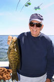 Man with Large Fish - Lake Ontario Smallmouth Bass. A picture of a man holding a large fish, a Smallmouth Bass, caught on Lake Ontario near Oswego, New York royalty free stock photography