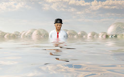 Man with large ideas surrounding him. In the form of classic light bulbs In flooded landscape Royalty Free Stock Photography