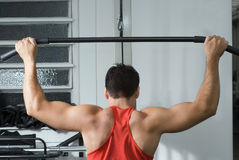 Man on the Lat Pull-Down Machine. Shot of the muscular back of a male athlete working out on a lat pull-down machine at the gym Stock Images