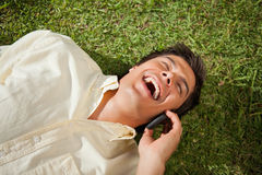Man laughing while making a call while using a phone as he lies Royalty Free Stock Images