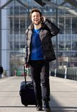 Man laughing on mobile phone while walking with luggage. Happy young man laughing on mobile phone while walking with luggage at station Royalty Free Stock Photo