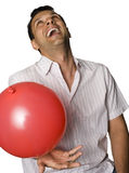 Man laughing and playing with baloon. Latino man laughing and playing with balloon Royalty Free Stock Image