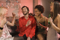 Man laughing with three women at a nightclub, all holding drinks. Royalty Free Stock Images
