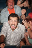Man Laughs Out Loud. Young Caucasian laughs out loud in theater Stock Photos