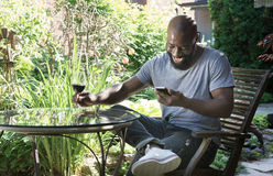 Man Laughs Reading Text Message in Garden Stock Images