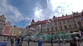A man launches huge soap bubbles entertain tourists in the old city center. Wide angle, slow motion. WROCLAW, POLAND - SEPTEMBER, 2018: A man launches huge soap stock video