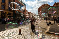 Man launches soap bubbles entertain tourists in the old city cen. WROCLAW, POLAND - APR 14, 2018: A man launches soap bubbles entertain tourists in the old city stock images
