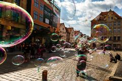 Man launches soap bubbles entertain tourists in the old city cen. WROCLAW, POLAND - APR 14, 2018: A man launches soap bubbles entertain tourists in the old city stock photography