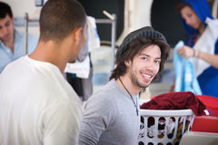 Man in Laundromat. Young handsome man with his friend smiles in the laundromat royalty free stock photography