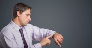 Man in lavender shirt looking at watch against grey background. Digital composite of Man in lavender shirt looking at watch against grey background Stock Images