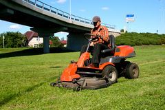 Man on a Lawn Tractor. Man on a riding lawn mower Stock Photo