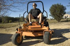 Man on lawnmower. A man preparing to ride a large orange landscaping piece of equipment known as a zero turn stock images