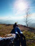 Man lay down and taking photo by mirror camera on neck. Snowy rocky peak of mountain. Royalty Free Stock Images