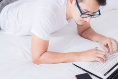 Man lay on white bad and use labtop for work royalty free stock images