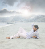 Man laying on beach. Young relaxed man laying on beach in calm blue morning light Stock Images