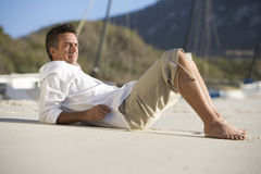 A man laying on a beach Stock Image