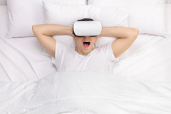 Man laying on bed and using VR goggles Royalty Free Stock Images