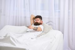 Man laying on bed, watching tv, white curtains on background. Guy on serious face using remote control for switch. Channel. Macho with beard holds smartphone as Royalty Free Stock Images