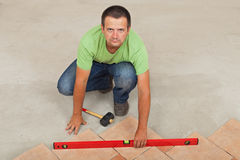 Man laying ceramic floor tiles - checking with a level, top view Stock Photo