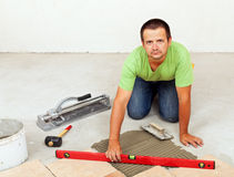 Man laying ceramic floor tiles on concrete floor Royalty Free Stock Photography