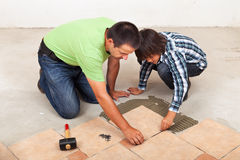 Man laying ceramic floor tiles helped by his son. To evenly space the pieces Stock Images