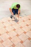 Man laying ceramic floor tiles Stock Image