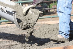 Man laying concrete. Detail of a labourer laying concrete on a building site Royalty Free Stock Photography