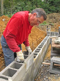 Man laying concrete block wall Stock Photo