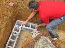 Man laying concrete block wall Stock Images