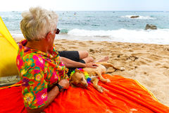 Man laying with dog at the beach Royalty Free Stock Image