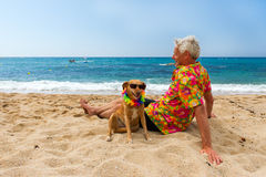 Man laying with dog at the beach Royalty Free Stock Photos
