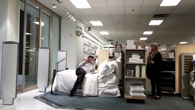 Man laying down on display bed and talking to his friend on phone. Inside The Bay store stock video footage