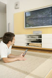 Man Laying Down on Floor Watching TV Stock Photo