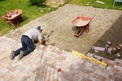 Man laying down paver. Young man installing paver bricks for large patio Royalty Free Stock Photography