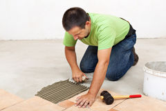 Man laying floor tiles - spreading the adhesive Stock Photo